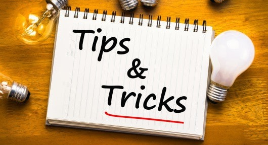 Tips and Tricks text on notebook with glowing light bulbs